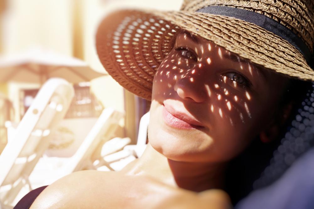 Jeune femme qui a bien préparé son bronzage et qui se protège du soleil sous un chapeau