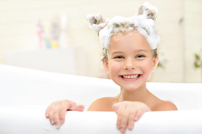 Une petite fille soigne ses poux naturellement dans son bain
