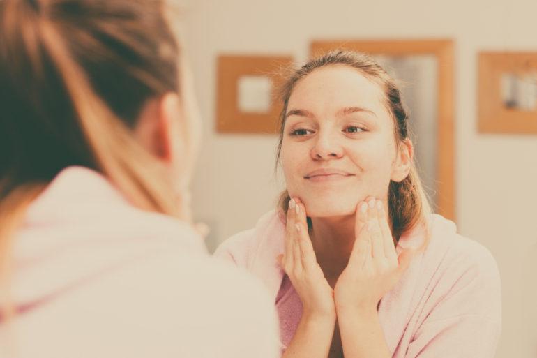Une jeune femme nettoie sa peau durant son soin du visage de routine quotidienne